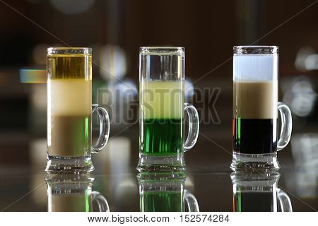 Variety of colorful green blue yellow red and white beautiful alcohol sweet shooters shots cocktail fresh beverage in small glasses standing in row on bar studio closeup horizontal picture