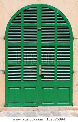 An italian style house entrance with green door and shutters
