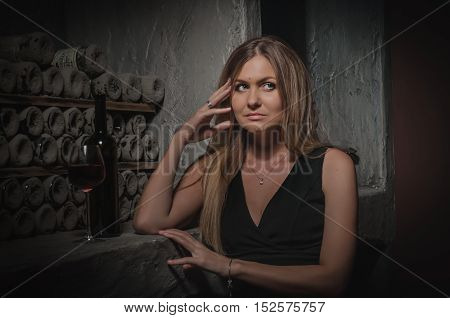 Beautiful girl in black cocktail dress in the old wine cellar