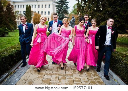 Four groomsmen and four bridesmaids having fun stylish friends at wedding