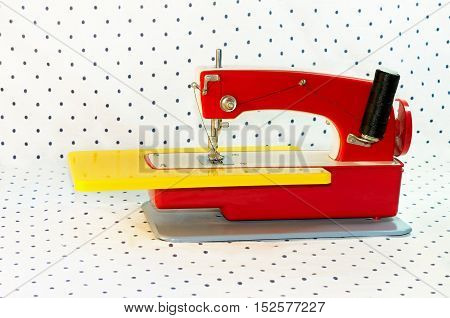 sewing machine children's toy of red color on a white background with points