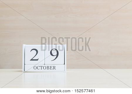 Closeup surface white wooden calendar with black 29 october word on blurred brown wood desk and wood wall textured background with copy space selective focus at the calendar