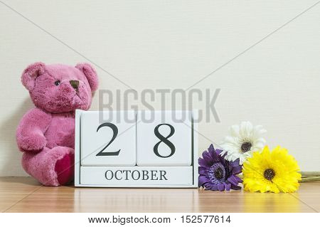 Closeup surface white wooden calendar with black 28 october word on brown wood desk and cream color wallpaper in room textured background with copy space selective focus at the calendar