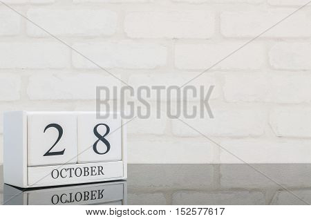 Closeup white wooden calendar with black 28 october word on black glass table and white brick wall textured background with copy space selective focus at the calendar