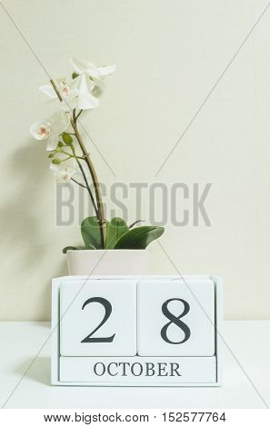 Closeup white wooden calendar with black 28 october word with white orchid flower on white wood desk and cream color wallpaper in room textured background selective focus at the calendar