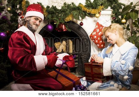 portrait of Santa Claus with Snow Maiden at Cristmas tree, lifestyle real people concept