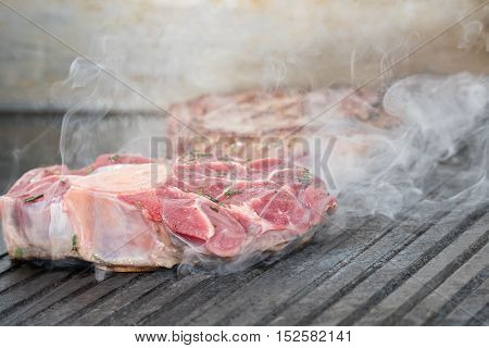 Two pieces of raw meat fried on a black electric grill, which is a lot of smoke
