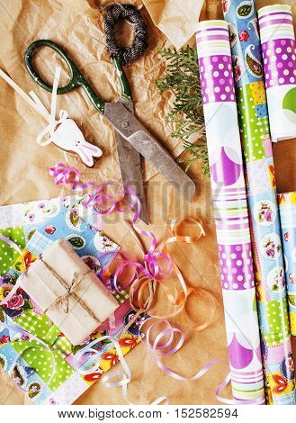 lot of stuff for handmade gifts, scissors, ribbon, paper with countryside pattern, ready for holiday concept, nobody home, Christmas decoration close up