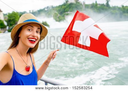 Young female tourist with swiss flag near the famous Rhine waterfall in Switzerland