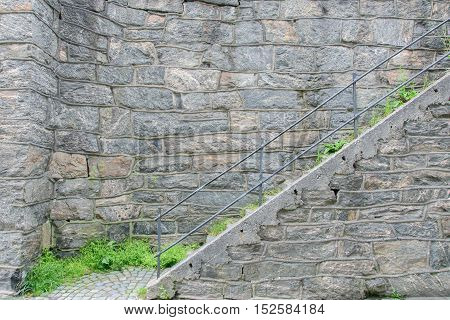 pedestrian staircase with metal handrails. Stone wall