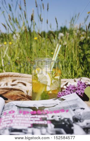 Summer relax with fresh lemon drink in the jar on green field background