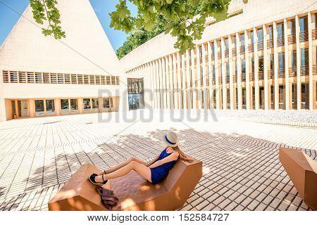 Vaduz, Liechtenstein - July 01, 2016: Young female tourist sits on the bench near the Parliament building in Vaduz, Liechtenstein