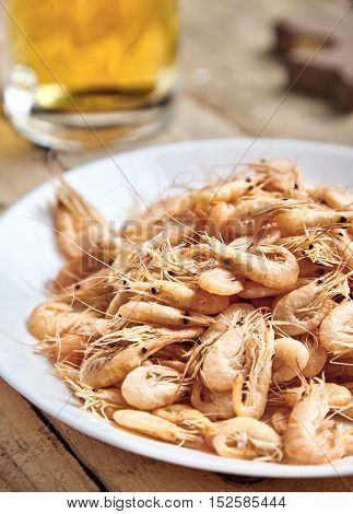 Heap of delicious, hot boiled shrimp or prawns in the shell on white plate, beer mug behind. Tasty seafood. Easy cooked, gourmet food, perfect snack for beer. Wooden, rustic background