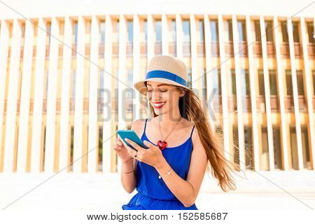 Young woman in blue dress using phone outdoors on the modern wall background