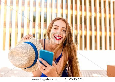 Portrait of a young smiling woman with phone outdoors on the modern wall background
