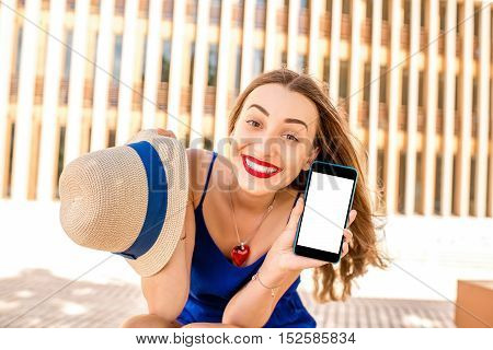 Young smiling woman in blue dress showing phone with white screen outdoors on the modern wall background
