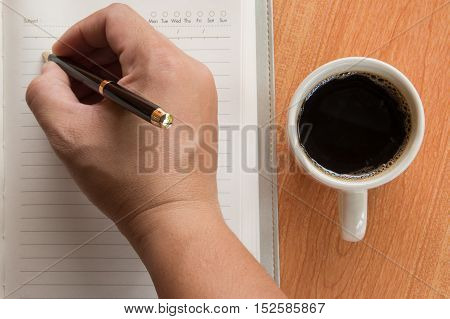 Hand of man writing in open notebook on wooden desk background with cup of coffee, top view