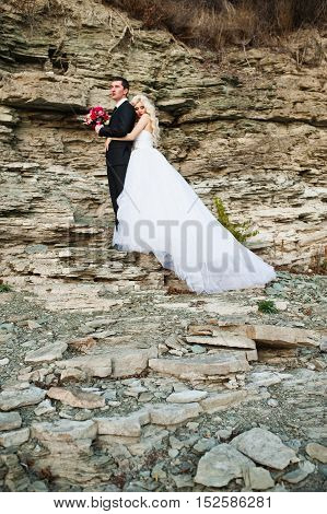 Charming Bride And Elegant Groom On Landscapes Of Mountains And Rocks