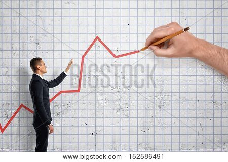 Businessman indicating a large hand how to draw a graph. Investment and finance. Successful management. Business control.