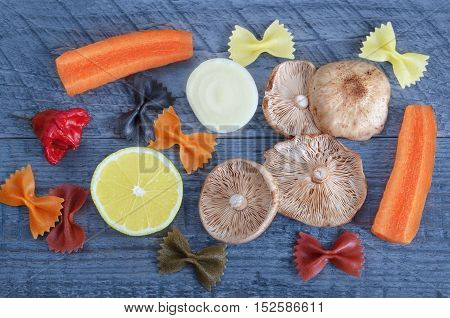 Raw mushrooms, vegetables, half of lemon and pasta on a blue wooden background.