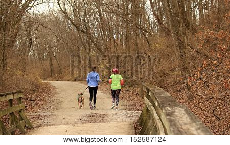 Two women running  on the trail with a dog
