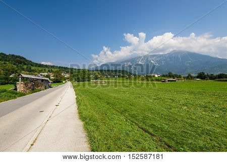 Pictorial field and an asphalt road on the background of mountain peaks, Bled, Slovenia.
