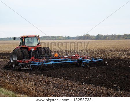tractor plowing the field after harvest in autumn