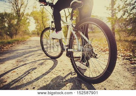 Athlete woman is running with her extreme mountain bike outdoors. wheel of a bicycle sports and a girl