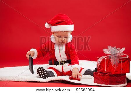 Beautiful little baby celebrates Christmas. New Year's holidays. Baby in a Christmas costume with gift and with the phone