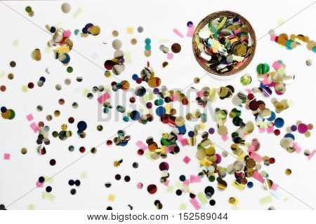 Over head view of bright, colorful confetti and cocktail glass filled with confetti.
