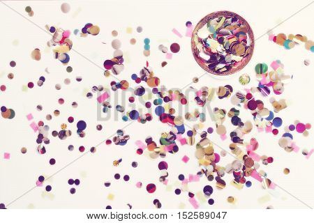 Over head bright, colorful confetti background with cocktail glass filled with confetti