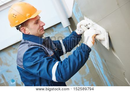 worker at plastering facade work