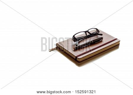 Glasses and pen on top of brown agenda with white background