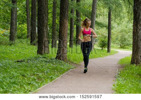 Young slim woman jogging in a park looking to smart watch