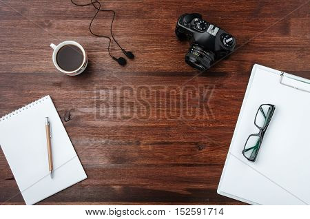 Coffee and camera on dark wood table with paper pen glasses. Top view. Wood texture