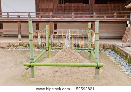 UJI JAPAN - JULY 27 2016: Tatesuna near Oratory Haiden of Ujigami Shinto Shrine in Uji city near Kyoto. Tatesuna are pair of standing cones of sand construed as allusions to pair of sacred mountains