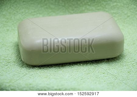 Light soap bar on green towel. Bathroom