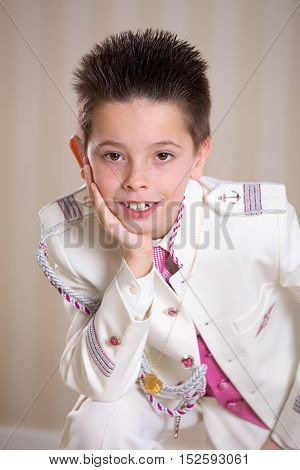 Young Boy Resting His Head On His Hand In His First Holy Communion