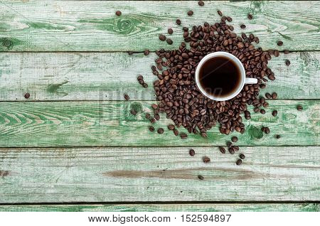 Cup coffee with beans on green wood table. Rustic wood texture. Top view