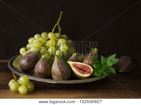 Fresh fruit: figs, grapes and mint leaves on a wooden table