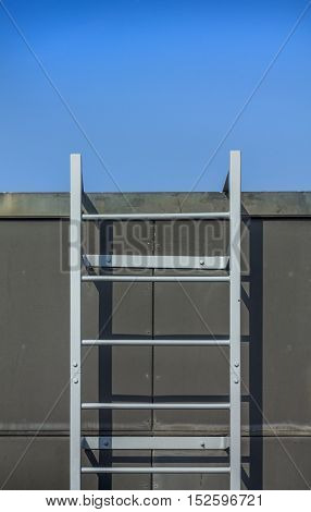 The ladder on a roof of the building with a sky on the background