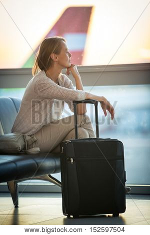 Young female passenger at the airport, waiting for her flight boarding call (color toned image; shallow DOF)