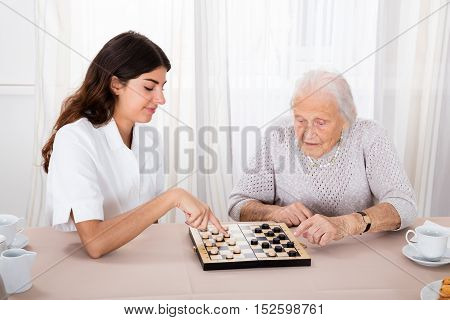Senior Woman Playing Checkers Game With Young Nurse On Table