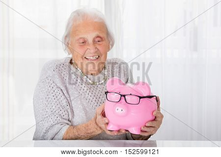 Happy Senior Woman Holding Piggybank At Home