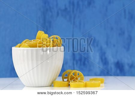 A bowl of cavatappi pasta on a blue bakground selective focus with copy space.