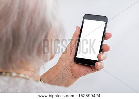 Close-up Of Senior Woman Using Smartphone With Blank Screen At Home