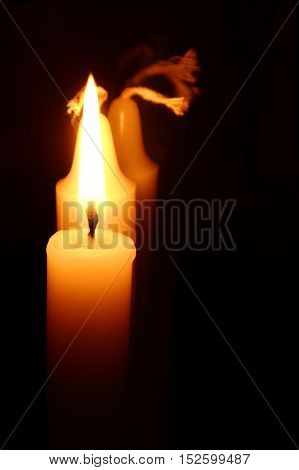 closeup of a burning candle against the black background