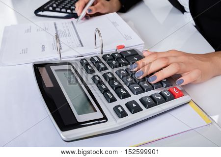 Close-up Of Young Businesswoman Calculating Tax Using Calculator In Office