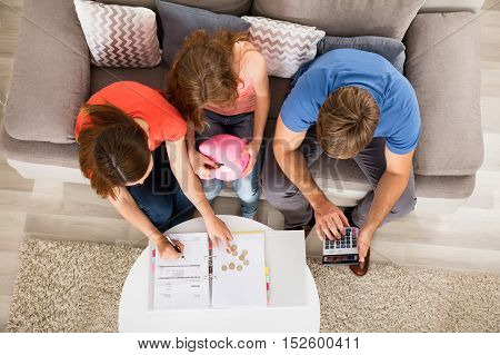 High Angle View Of A Family Sitting On Sofa Calculating Bill