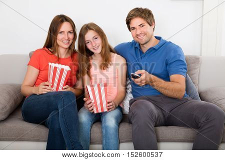 Smiling Family With Popcorn Sitting On Sofa Watching Television